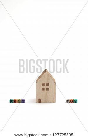 Miniature houses with alphabet blocks that spell buy and rent on white background.