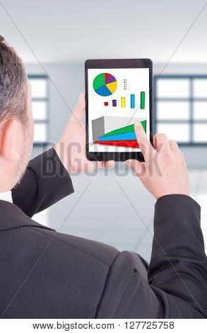 Modern business man holding wireless tablet with financial charts or graphs