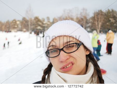 young adult woman in a white winter cap and glasses.
