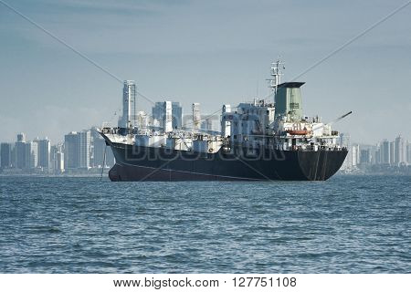 View of a large cargo ship anchored and the city skyline at the background, Panama