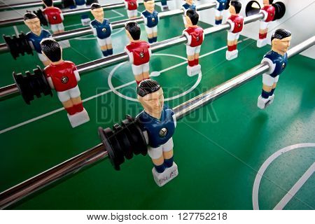 Miniature figures of players fixed on rods .