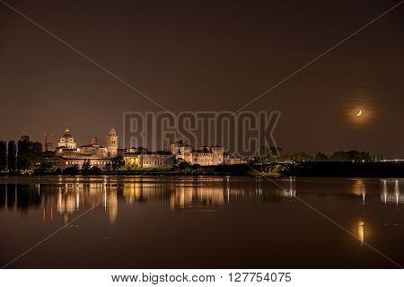 Mantua, Italy - April 25, 2015: Mantua nightscape reflection on the river