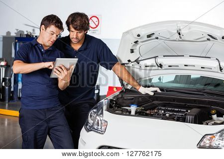 Mechanics Using Tablet Computer By Damaged Car