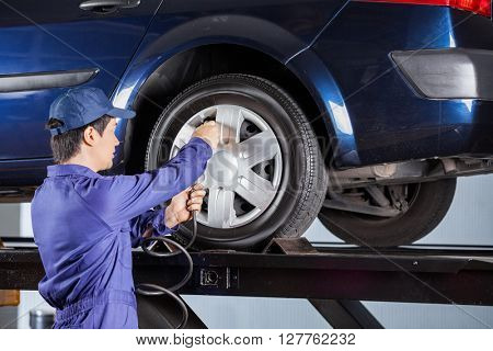 Repairman Inflating Tire Of Lifted Car