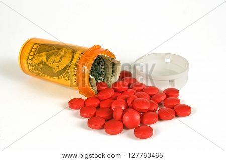Medical expenses concept.  Pill bottle with money inside and red pills spilling out.
