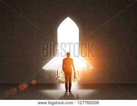 Start up concept with businessman holding briefcase and standing in front of rocket shaped gap in wall revealing sunlit New York city view