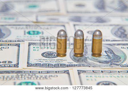 Three silver pistol Bullets on dollar bills