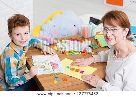 Nice smiling occupational therapist working with little boy with adhd. Teaching the kid new words