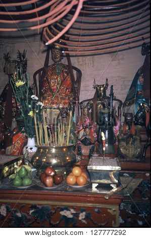 HONG KONG - CIRCA 1987: Fruits have been offered to sacred images standing on an altar in the Man Mo Miu Temple.