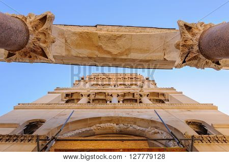 Underneath the east Peristyle looking up at the Corinthian column capitals arch and Bell Tower