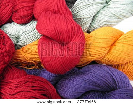 Different Colored yarn skeins piled up together.