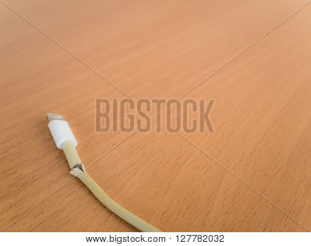 Closeup the Broken Smartphone Charger Cable on Wooden Background Copy Space
