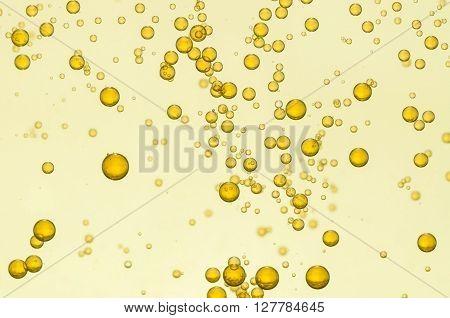 Golden fizz bubbles float over a light background