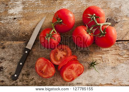 Preparing sliced ripe red tomatoes on a rustic wooden kitchen counter with a paring knife overhead view of sliced and whole tomatoes on the vine