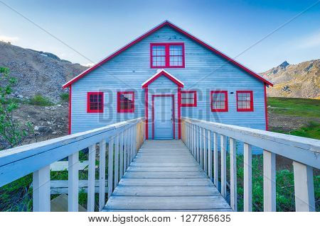 Wood building painted blue with red trim on the Independence Gold Mine from the Alaskan Gold Rush.