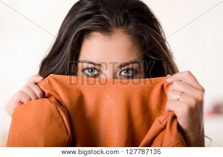 Headshot attractive brunette facing camera covering half her face with orange clothing, white studio background.