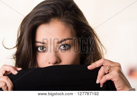 Headshot attractive brunette facing camera covering half her face with black clothing, white studio background.