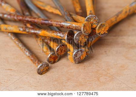 Rusty nail pile on brown wooden background