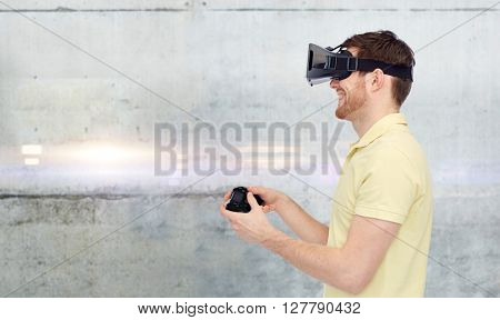 3d technology, virtual reality, entertainment and people concept - happy young man with virtual reality headset or 3d glasses playing with game controller gamepad over gray concrete wall background poster
