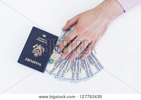Male hand with american passport and dollars on white surface
