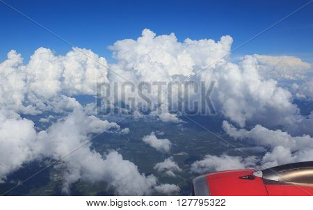 aerial top view from air plane see green field rural and wing aircraft engine clear white cumulus cloud and cloudscape on blue sky