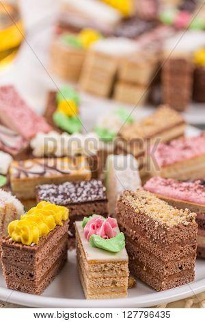 Assorted different mini cakes with cream, studio shot