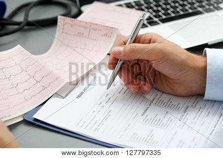 Male Doctor Hands With Cardiogram Chart On Clipboard Pad