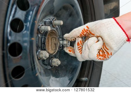 Man's Hand Unscrews The Nuts On The Car Wheel, Close-up Shot