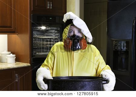 Mature woman wearing a HazMat suit standing in a kitchen with singed face holding roasting pan with chefs hat.