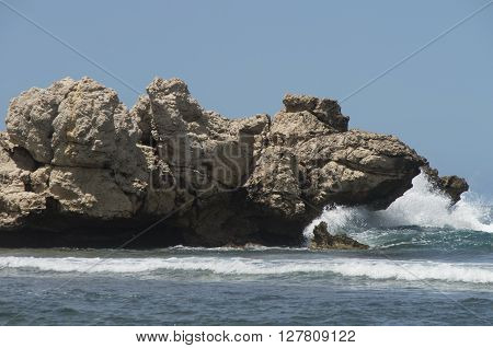 Waves crash against a large rock outcrooping along the shoreline in Labdaee Hati