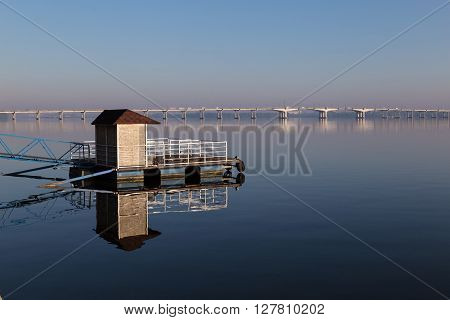 quay afloat reflected on mirror water surface at clear summer morning. bridge across the Dnipro river in the background . Dnepropetrovsk. Ukraine