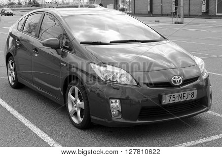 Muiden, The Netherlands - April 30, 2016: Gray Toyota Prius Hybrid parked on a public parking lot in the city of Muiden.