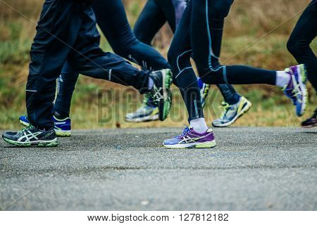 closeup of feet group athletes men running down road during marathon