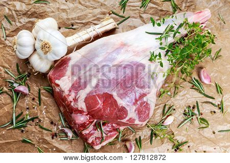Raw lamb leg on crumpled paper background with herbs