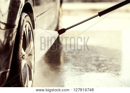 Car wash with high pressure washer, close up