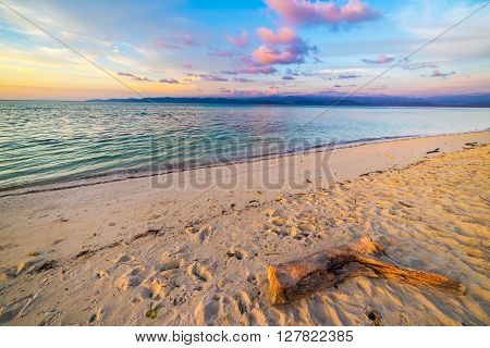 Pastel colored sky clouds and seascape at dusk. Wide angle view from sandy beach with trunk fragment in the foreground. Tanjung Karang Sulawesi Indonesia.