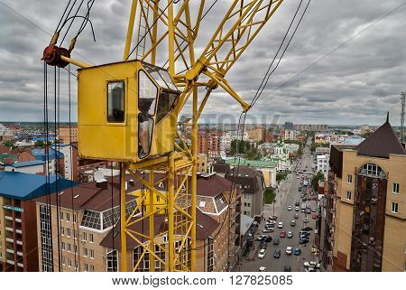 Tyumen Russia - May 23 2008: ?onstruction of 18 floor brick residental house at intersection of Gercena and Chelyuskincev streets. Lifting crane on construction site