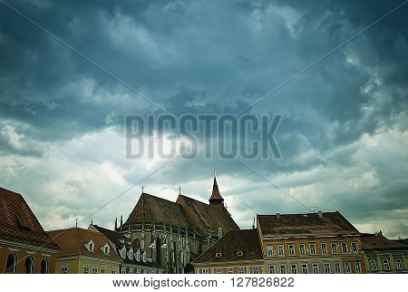 Illustration of old medieval houses above a cloudy sky in the historic center of Brasov city. Oil paint filter