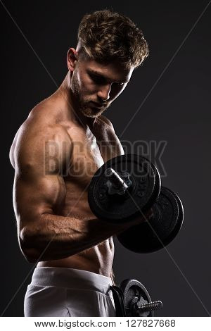 Handsome Young Bodybuilder Training With Dumbbells, On Grey Background