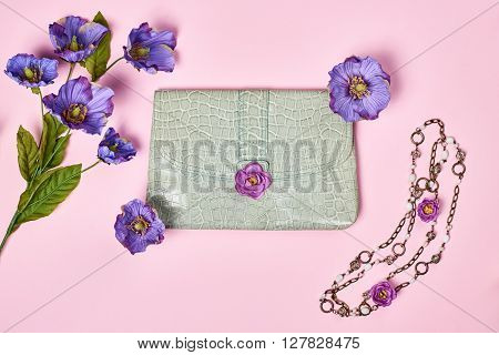 Overhead outfit Fashion Ladies, accessories. Glamor creative  handbag clutch, flowers, necklace. Focus on Pastel Colors. Unusual modern elegant essentials, minimalism.Top view, pink background
