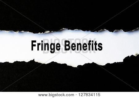 Business concept - Fringe benefits words under torn paper