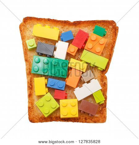 plastic toy blocks on toasted bread. food for thought. concept. isolated on white background
