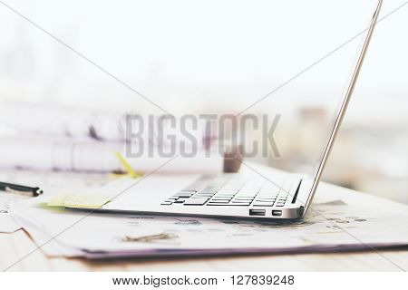 Sideview of notebook placed on wooden desktop with sketches on paper