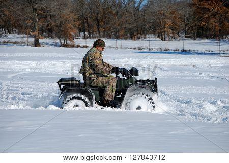 Man in camo riding quad wheeler through the snow.