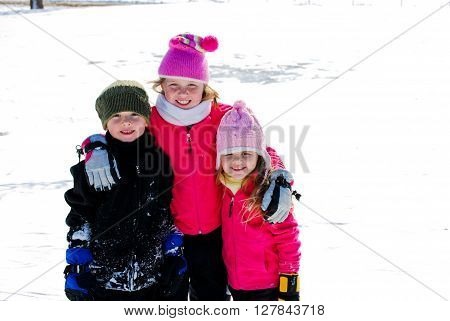 Two pretty girls and one cute boy huddled together smiling at camera.