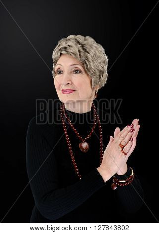 Portrait of spectacular 76-year-old woman wears brecciated red jasper agate bead necklaces bracelets heart pendant and rings. She dresses in black turtleneck shirt. The applauding women has on ash blonde wig. Upper body vertical shot on black background