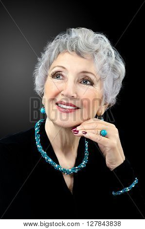 Facial portrait of senior woman wearing turquoise twisted bead necklace bracelet ring and earrings. Grey haired spectacular 76-year-old woman posing on black background. Vertical shot.