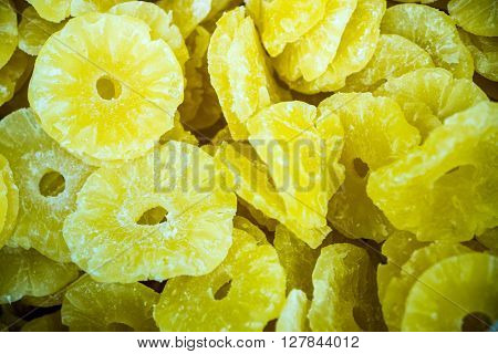 Close up view of dried pineapple slices in bulk.