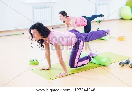 Wit women one leg extension kneeling kickbacks, exercise for lower back, hips and buttocks exercising at fitness club