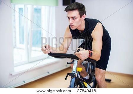 Athlete man biking in the gym, exercising his legs doing cardio training cycling bikes.